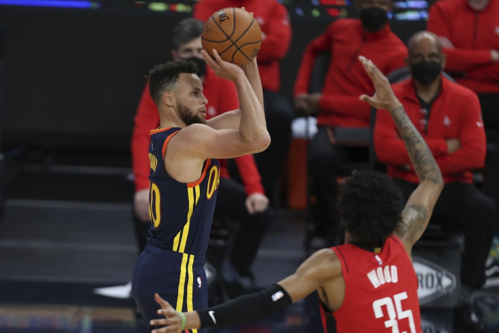 Golden State Warriors guard Stephen Curry, left, shoots against Houston Rockets forward Christian Wood during the second half of an NBA basketball gam...