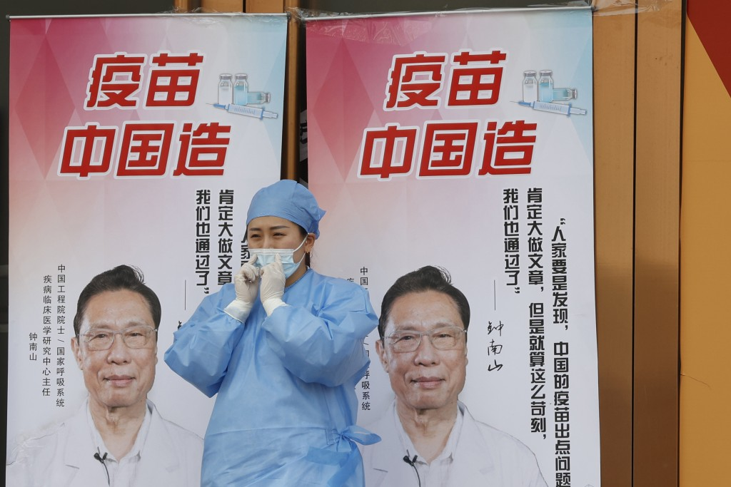 """A medical worker adjusts her mask near propaganda boards showing famed Chinese medical expert Zhong Nanshan and the words """"Vaccine China Made"""" outside..."""