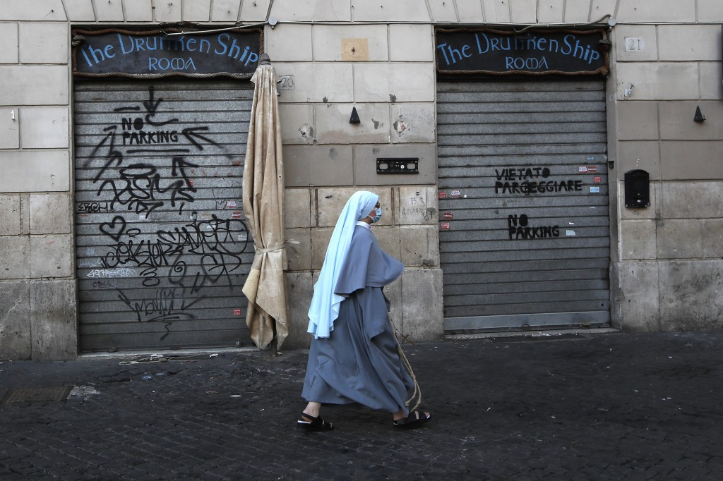 FILE - In this March 15, 2021, file photo, a nun wearing a face mask to curb the spread of COVID-19, walks past a closed shop in downtown Rome. Lofty ...
