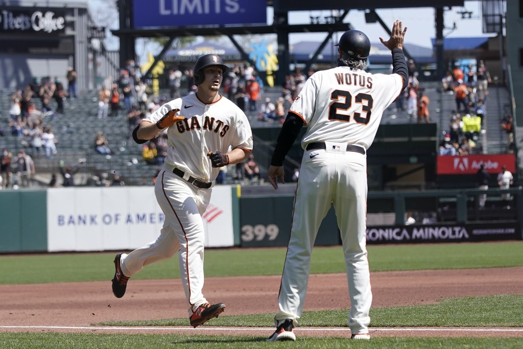 San Francisco Giants' Alex Dickerson, left, is congratulated by third base coach Ron Wotus, right, after hitting a solo home run against the Colorado ...