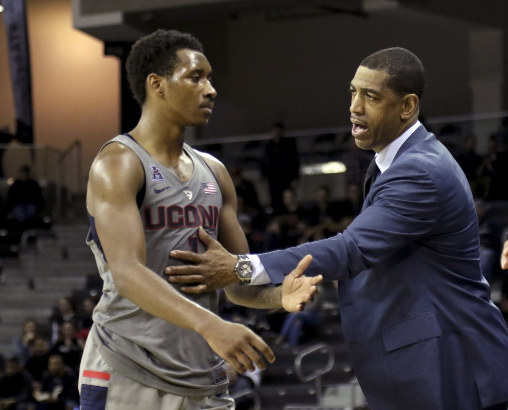 FILE - Connecticut head coach Kevin Ollie, right, talks with Christian Vital during the second half of an NCAA college basketball game against Cincinn...