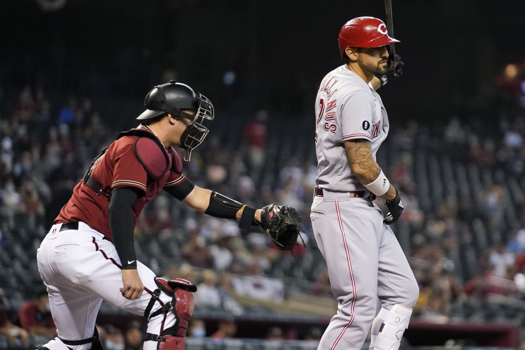 Arizona Diamondbacks catcher Carson Kelly, left, tags out Cincinnati Reds' Nick Castellanos, right, after a dropped third strike during the first inni...