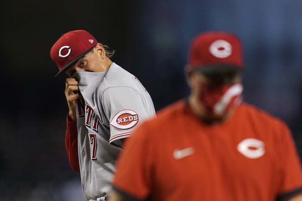 Cincinnati Reds starting pitcher Jose De Leon, left, wipes sweat from his face after getting a visit from Reds pitching coach Derek Johnson, right, as...