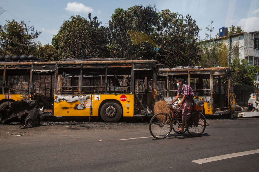 A man bikes past burnt public transport buses parked at Kyimyindaing township in Yangon, Myanmar Monday, April 12, 2021. Local news media reported tha...