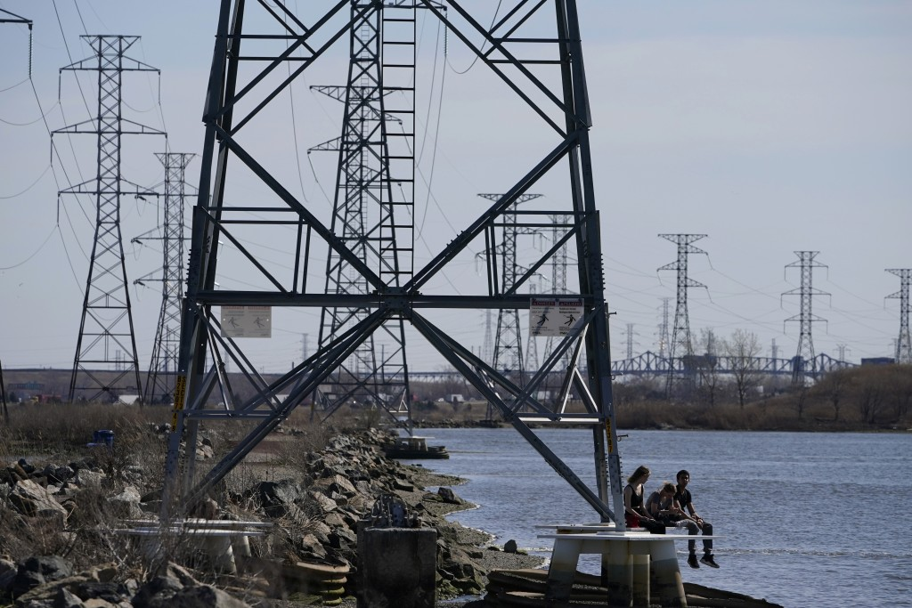 FILE - People sit at the base of a transmission tower in North Arlington, N.J., Tuesday, April 6, 2021. The Biden White House is amplifying the push f...