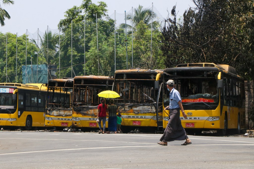 People look at a row of burnt public transport buses parked at Kyimyindaing township in Yangon, Myanmar Monday, April 12, 2021.  Local news media repo...