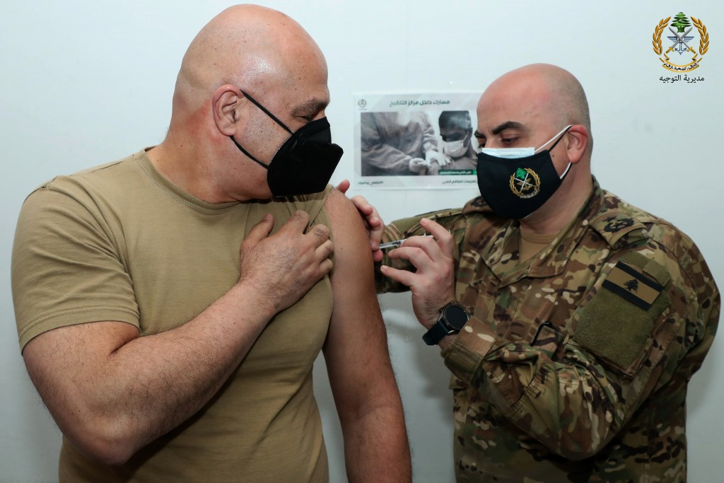 In this photo released by the Lebanese Army official website, Lebanese Army Commander Gen. Joseph Aoun, receives a Sinopharm COVID-19 vaccine, at one ...