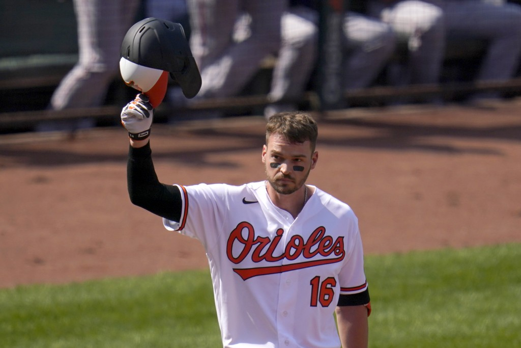 Baltimore Orioles' Trey Mancini tips his helmet as fans give him a standing ovation prior to batting against the Boston Red Sox during the first innin...