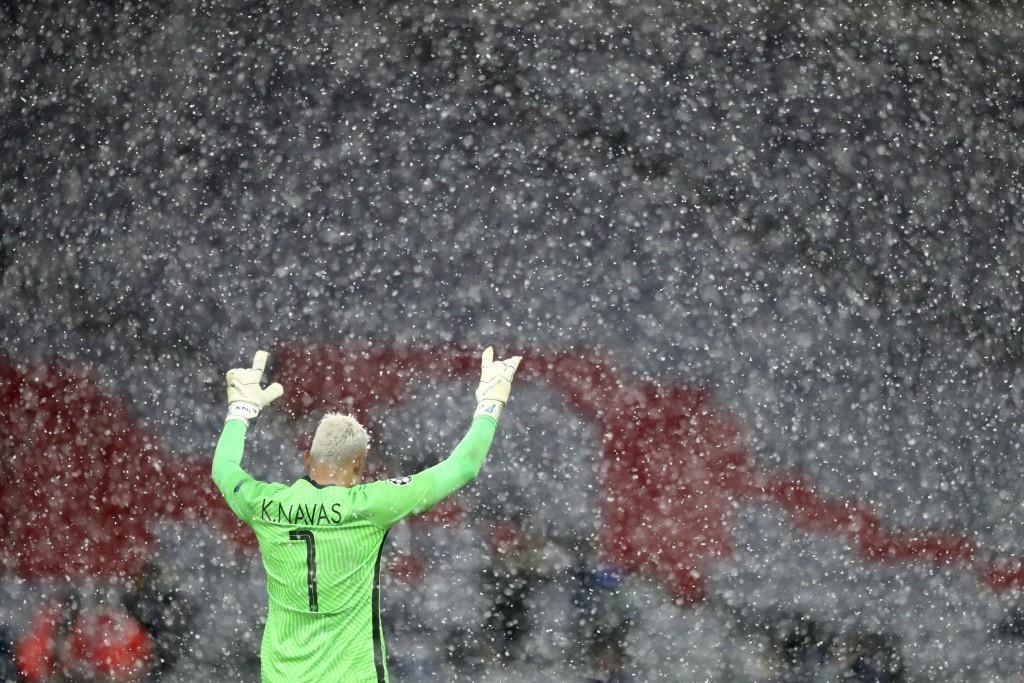 Snow falls as PSG's goalkeeper Keylor Navas reacts after the Champions League quarterfinal soccer match between Bayern Munich and Paris Saint Germain ...