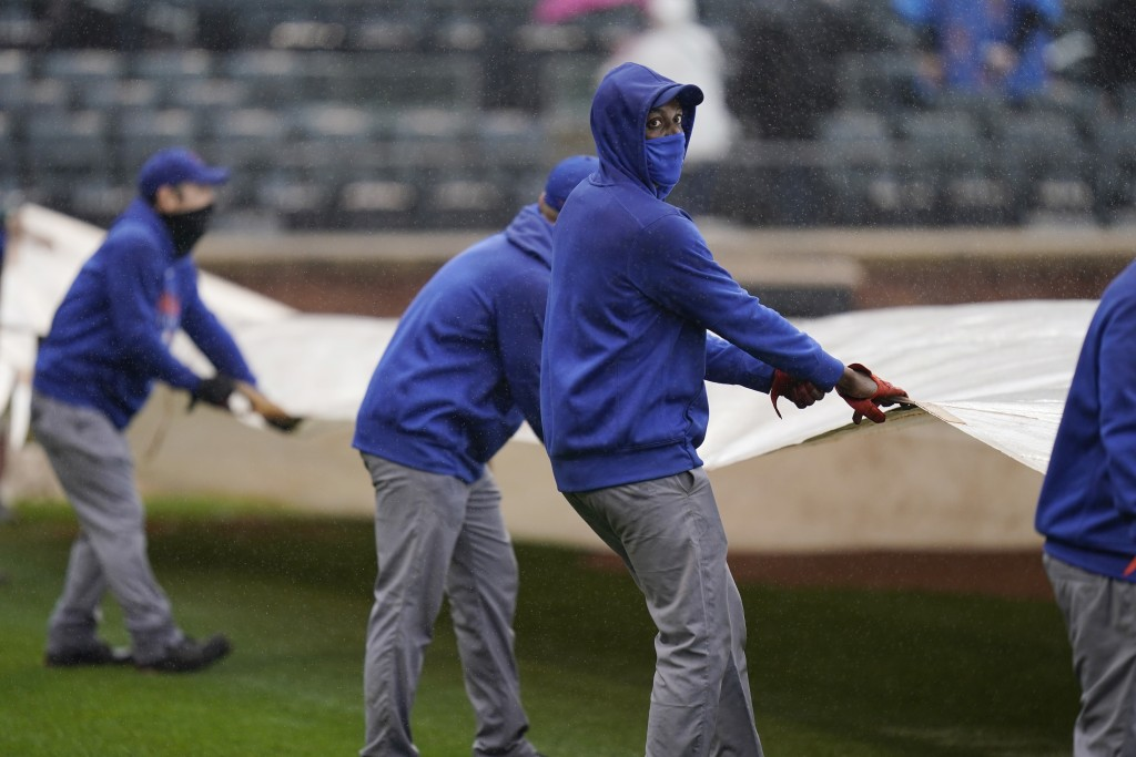 New York Mets employees put a tarp over the field during a delay in the first inning of a baseball game against the Miami Marlins at Citi Field, Sunda...
