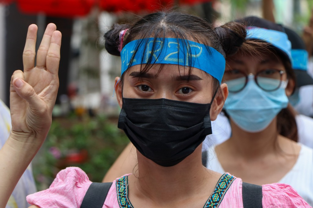 An anti-coup protester flashes the three-fingered salute while wearing a headband that reads R2P, which means Responsibility to Protect, during a gath...