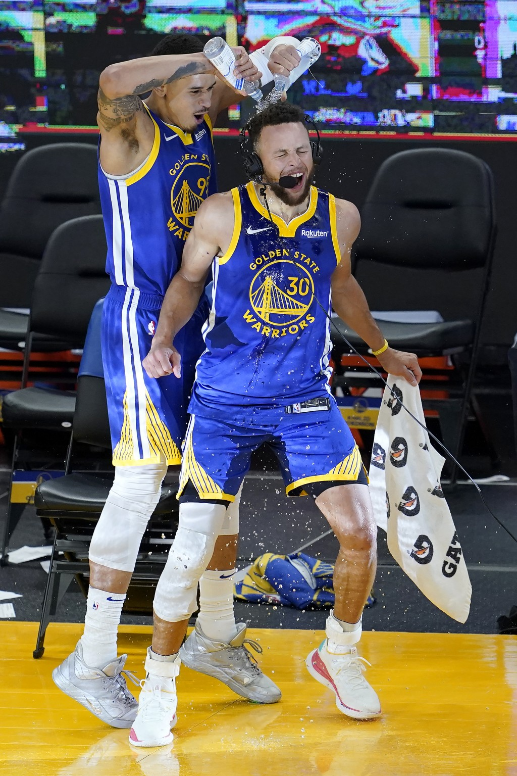 Golden State Warriors forward Juan Toscano-Anderson, left, pours water onto guard Stephen Curry (30) after the Warriors defeated the Denver Nuggets in...