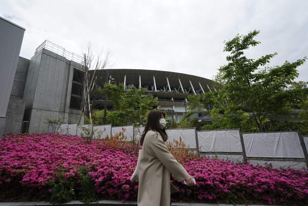 A woman wearing a protective mask to help curb the spread of the coronavirus walks near the Japan National Stadium, where opening ceremony and many ot...