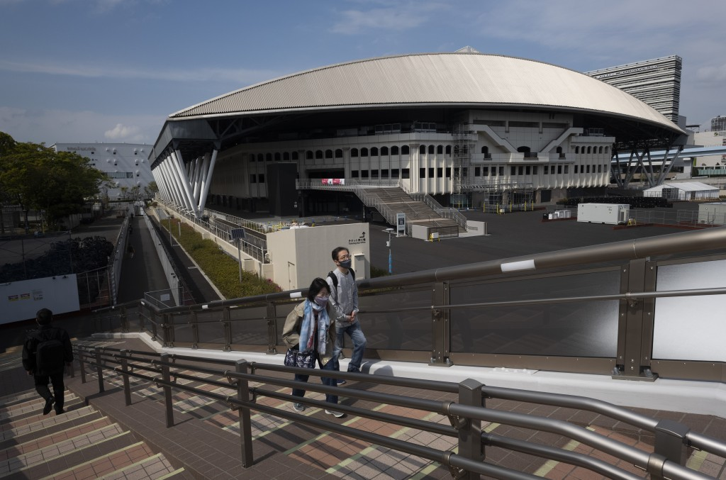 People walk past Ariake Colosseum, a venue planned to be used for the postponed Tokyo 2020 Olympic and Paralympic Games, in Tokyo Thursday, April 8, 2...