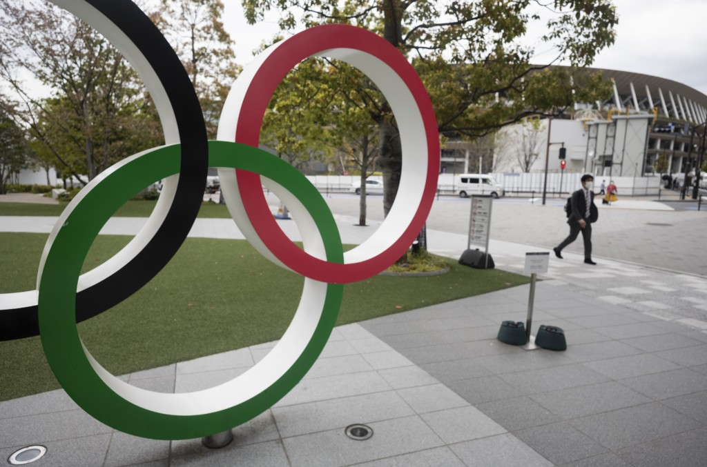 A man walks by a part of Olympic rings displayed at the Japan Olympic Museum situated across from the Japan National Stadium planned to be used for th...