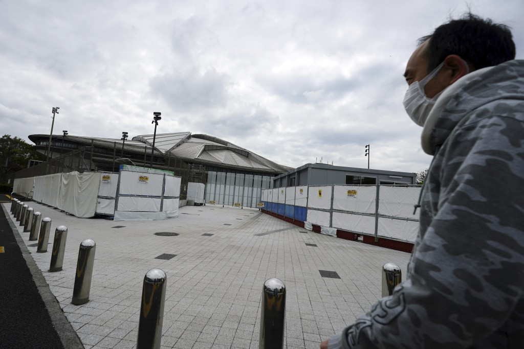 A man wearing a protective mask to help curb the spread of the coronavirus walks near Tokyo Metropolitan Gymnasium, one of venues for the postponed To...