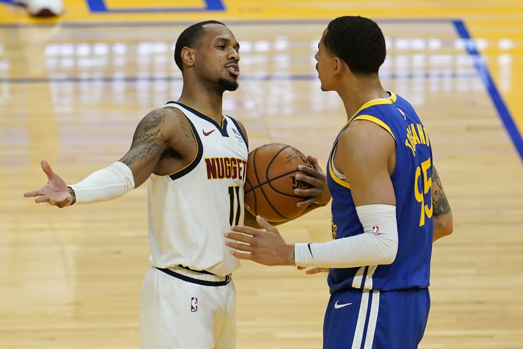 Denver Nuggets guard Monte Morris (11) gestures toward Golden State Warriors forward Juan Toscano-Anderson during the second half of an NBA basketball...