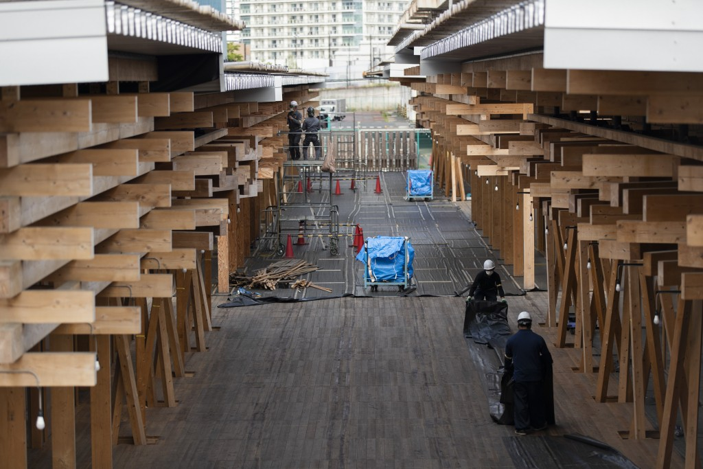 Construction workers fold a tarp sheet at a closed building complex being built as part of the athletes' village to be used during the postponed Tokyo...