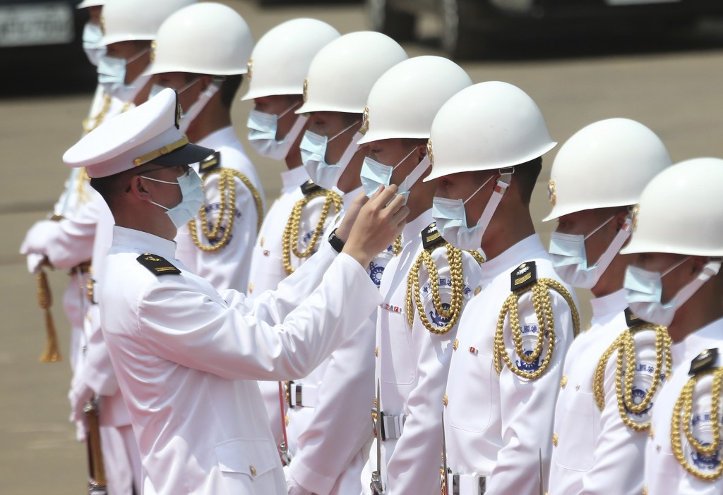 A Taiwan Navy honor guard captain adjusts team member's face mask during a launch ceremony for its first indigenous amphibious transport dock in Kaohs...