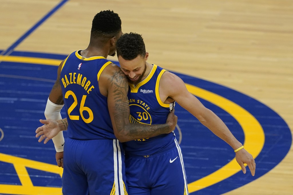 Golden State Warriors forward Kent Bazemore (26) is congratulated by guard Stephen Curry (30) after scoring against the Denver Nuggets during the seco...