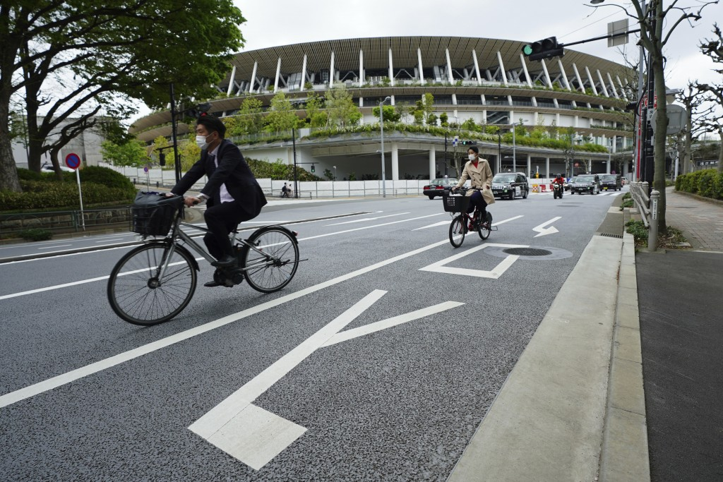 People wearing protective masks to help curb the spread of the coronavirus ride bicycles near the Japan National Stadium, where opening ceremony and m...