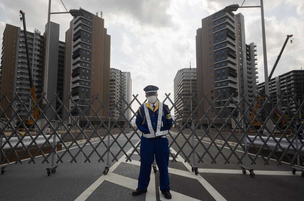 A guard stands in front of a fence to close off a construction site for the athletes' village to be used during the postponed Tokyo 2020 Olympic and P...