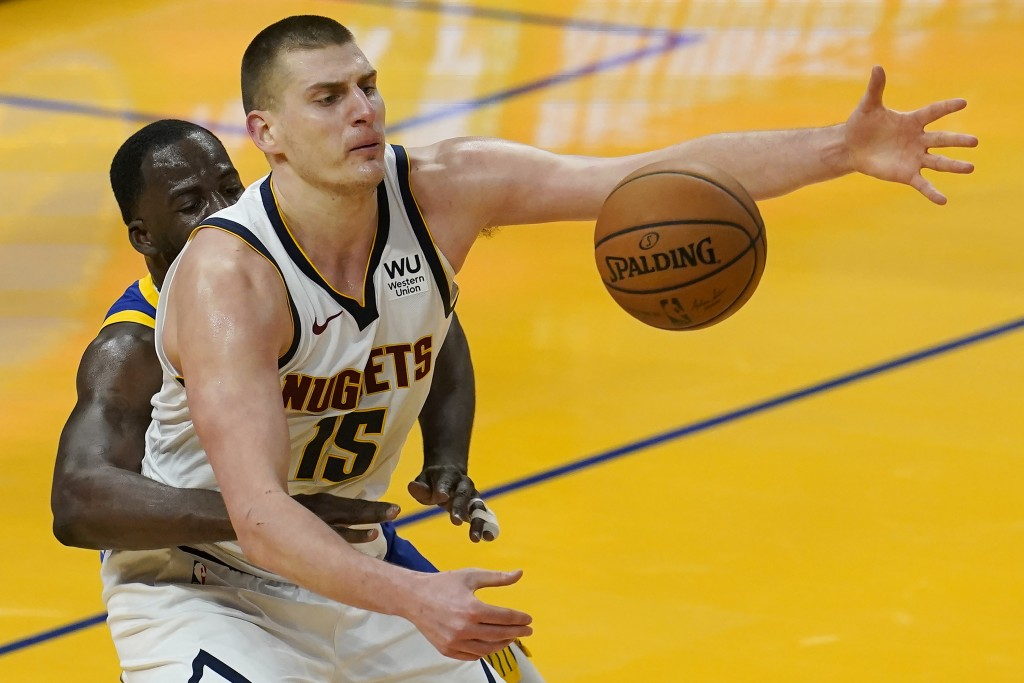 Denver Nuggets center Nikola Jokic (15) reaches for the ball while defended by Golden State Warriors forward Draymond Green during the second half of ...