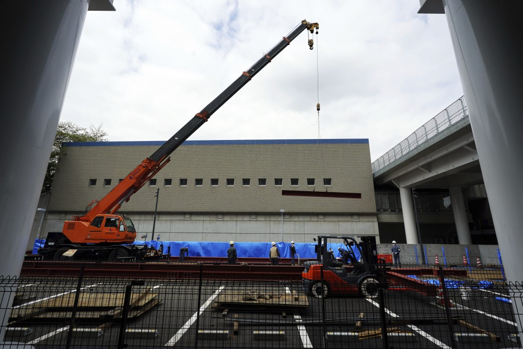 Construction workers lift a steel beam into position at Tokyo Metropolitan Gymnasium, one of venues for the postponed Tokyo 2020 Olympics Tuesday, Apr...