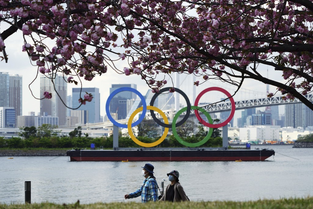 Under blooming cherry blossoms, people wearing protective masks to help curb the spread of the coronavirus walk with a backdrop of the Olympic rings f...