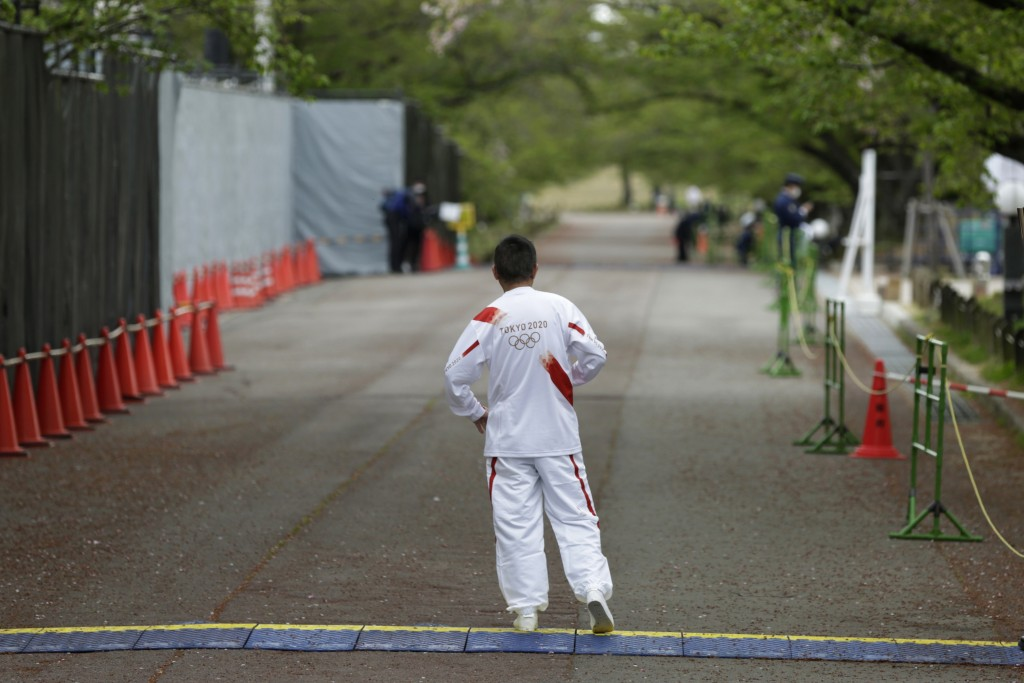 Entertainer Katsura Bunshi IV, participating as an Olympic torch relay runner, waits for his preceding runner during the first day of the Osaka round ...