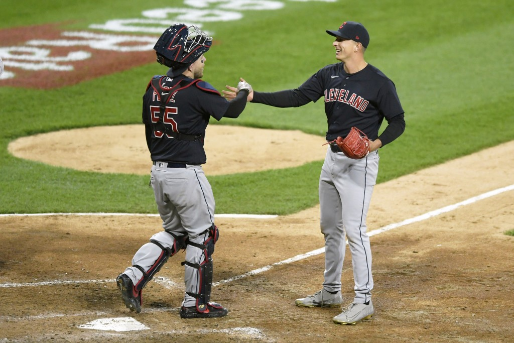 Cleveland Indians closing pitcher James Karinchak right, celebrates with catcher Roberto Perez left, after defeating the Chicago White Sox 2-0 in ten ...