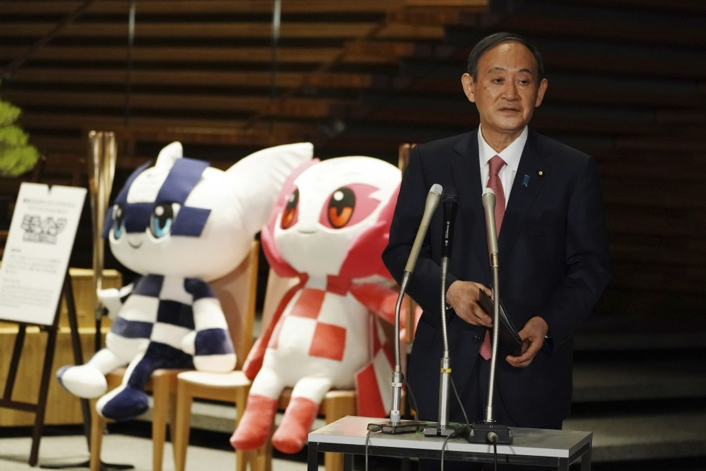 FILE - In this April 9, 2021, file photo, Japanese Prime Minister Yoshihide Suga, next to the mascots of Tokyo 2020 Olympic and Paralympic Games, spea...