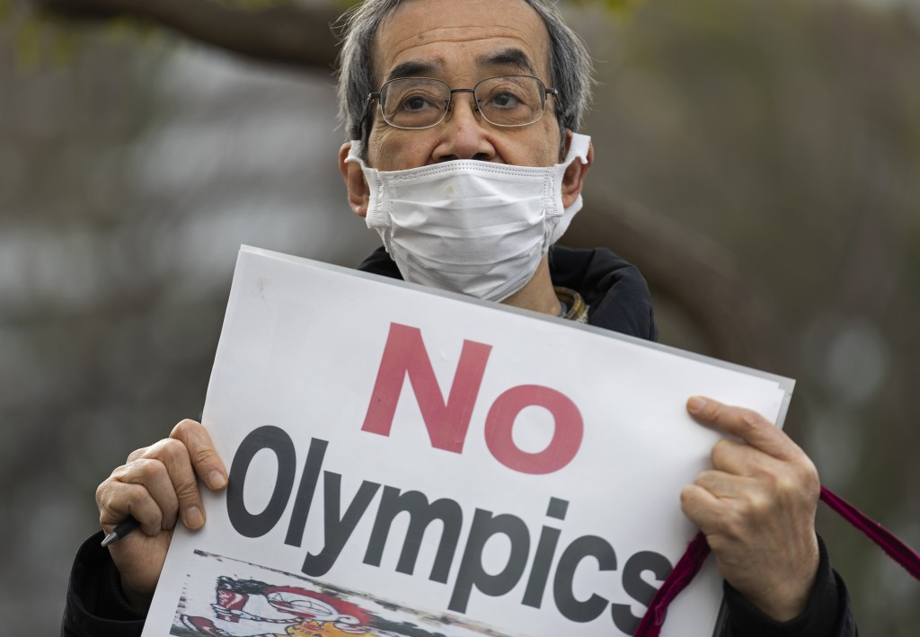 FILE - In this Feb. 12, 2021, file photo, a demonstrator holds a sign protesting the planned Tokyo 2020 Olympic games near a building where Yoshiro Mo...