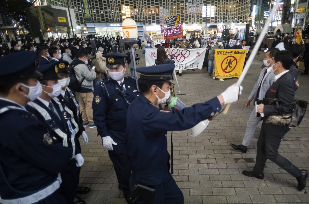 FILE - In this March 25, 2021, file photo, police officers start moving to secure streets as protesters and their supporters, background, start their ...
