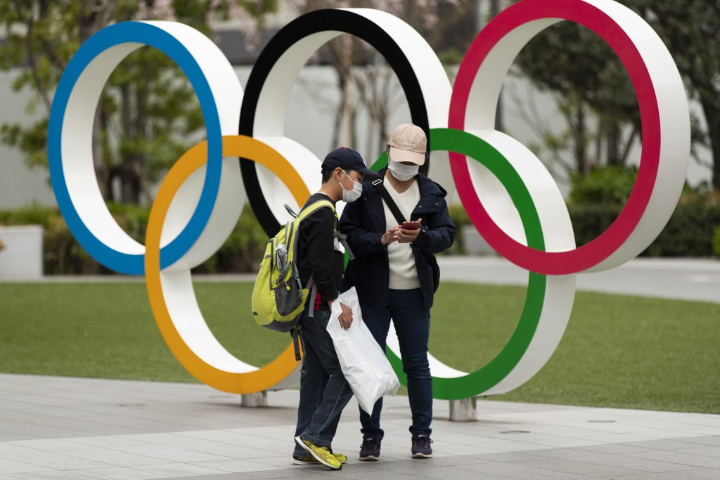 A boy looks at a cellphone after his mother took pictures of him in front of a display of the Olympic rings at the Japan Olympic Museum in Tokyo on Fr...