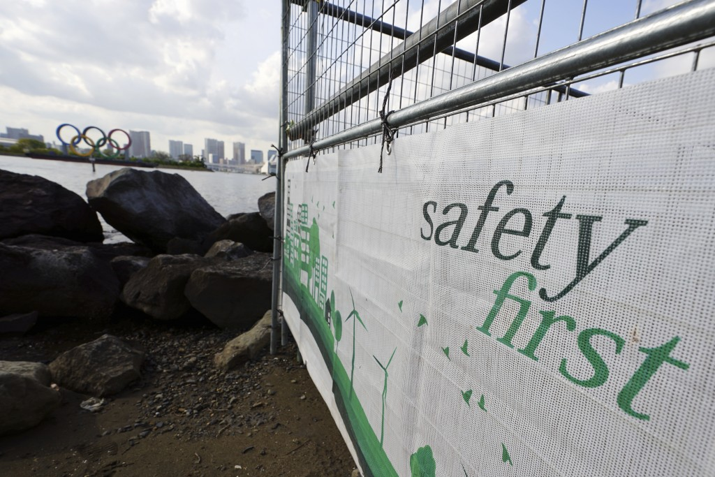"""A construction fence featuring the words """"Safety First"""" with a backdrop of the Olympic rings floating in the water in the Odaiba section Thursday, Apr..."""