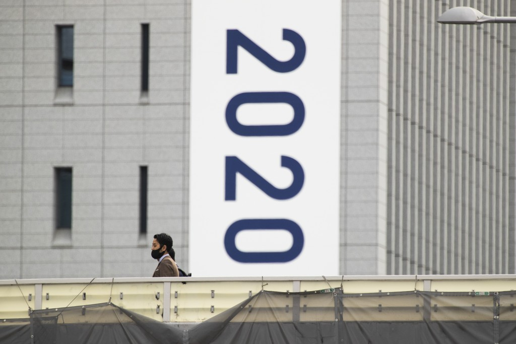 People wearing face masks walk on a crossover bridge near a banner to promote the rescheduled Tokyo 2020 Olympic Games in Tokyo Friday, April 2, 2021....