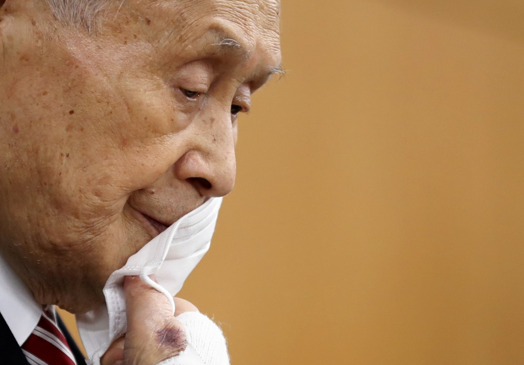 FILE - In this Feb. 4, 2021, file photo, Yoshiro Mori, the president of the Tokyo Olympic Organizing Committee, takes off his protective face mask as ...