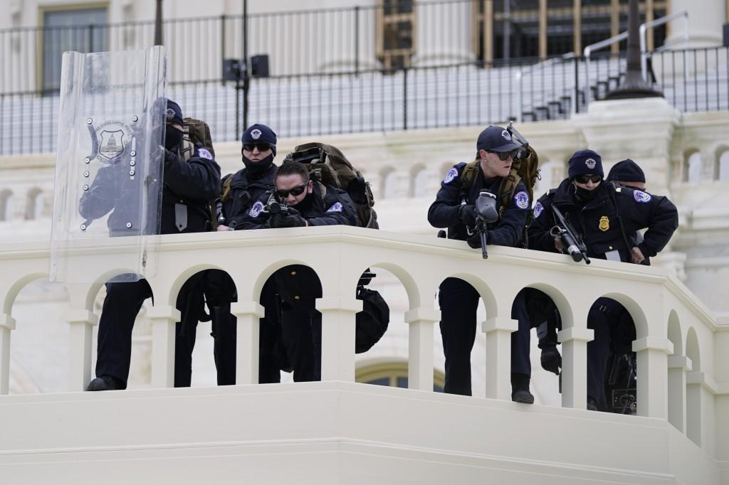 FILE - In this Jan. 6, 2021, file photo, police keep a watch on demonstrators who tried to break through a police barrier at the Capitol in Washington...