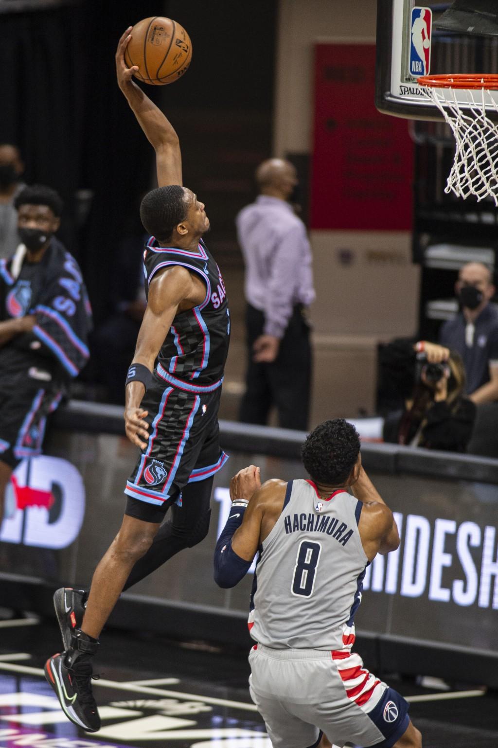 Sacramento Kings guard De'Aaron Fox (5) dunks in front of Washington Wizards forward Rui Hachimura (8) during the second quarter of an NBA basketball ...