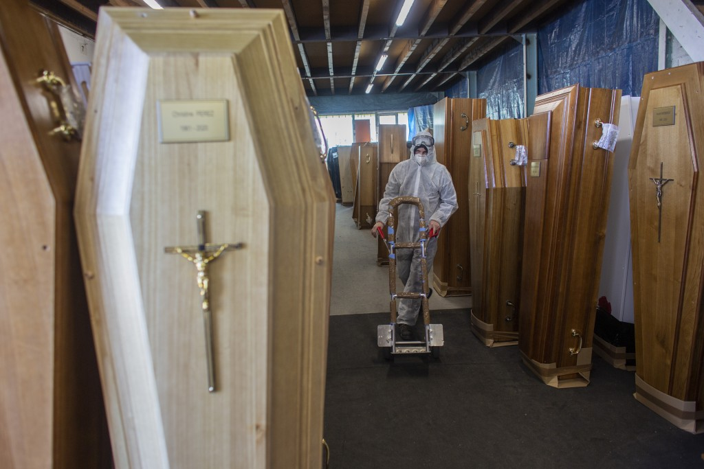FILE - In this April 14, 2020 file photo, a worker goes to pick up a coffin at a coffin design company in Ris Orangis , outside Paris. France is expec...