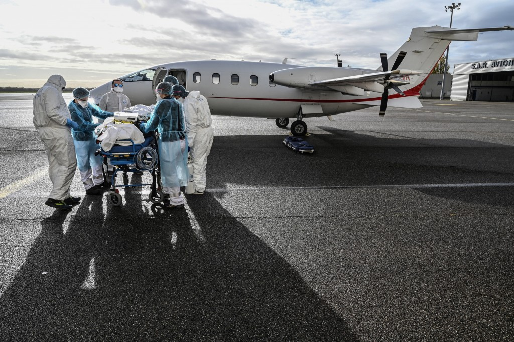 FILE - In this Nov. 16, 2020 file photo, medical staff transport a patient affected with COVID-19 to be evacuated to another hospital, at Bron airport...