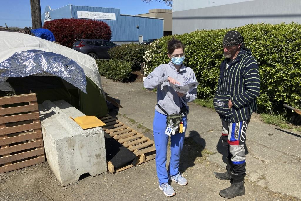 Moira Andrews, a street outreach nurse for Neighborcare Health, speaks with Charles Ussery, 52, who lives in an encampment in the Georgetown neighborh...