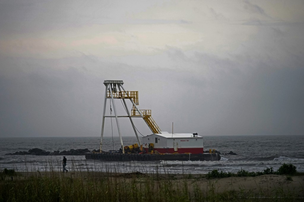A man who did not want to be identified surveys his company's barge that ran aground during a storm on Tuesday, that also capsized a lift boat, killin...