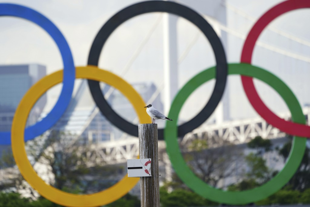 A bird rests with a backdrop of the Olympic rings floating in the water in the Odaiba section Thursday, April 8, 2021, in Tokyo. Two top officials of ...