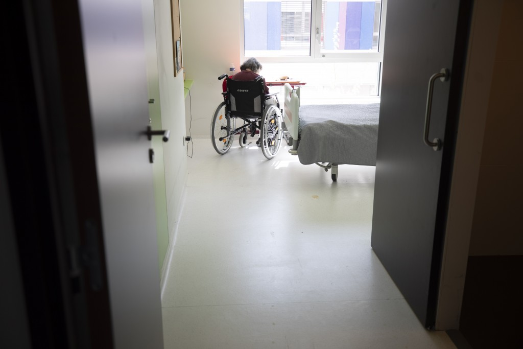 FILE - In this April 14, 2020 file photo, a resident sits in her room after being tested with COVID-19 in a nursing home in Bergheim, eastern France. ...