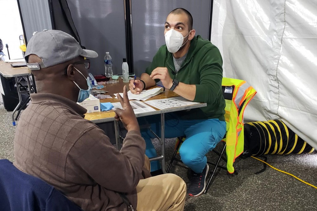 In this March 12, 2021 photo provided by Unity Health Care, Othon Sosua, right, talks with a patient during a vaccination drive in Washington, D.C. Ho...