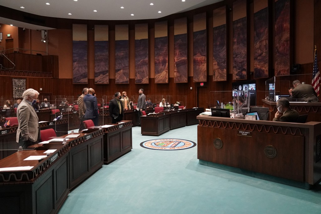 FILE - In this Feb. 18, 2021 file photo State representatives gather at the Capitol, in Phoenix. Two years after Arizona lawmakers repealed a law barr...