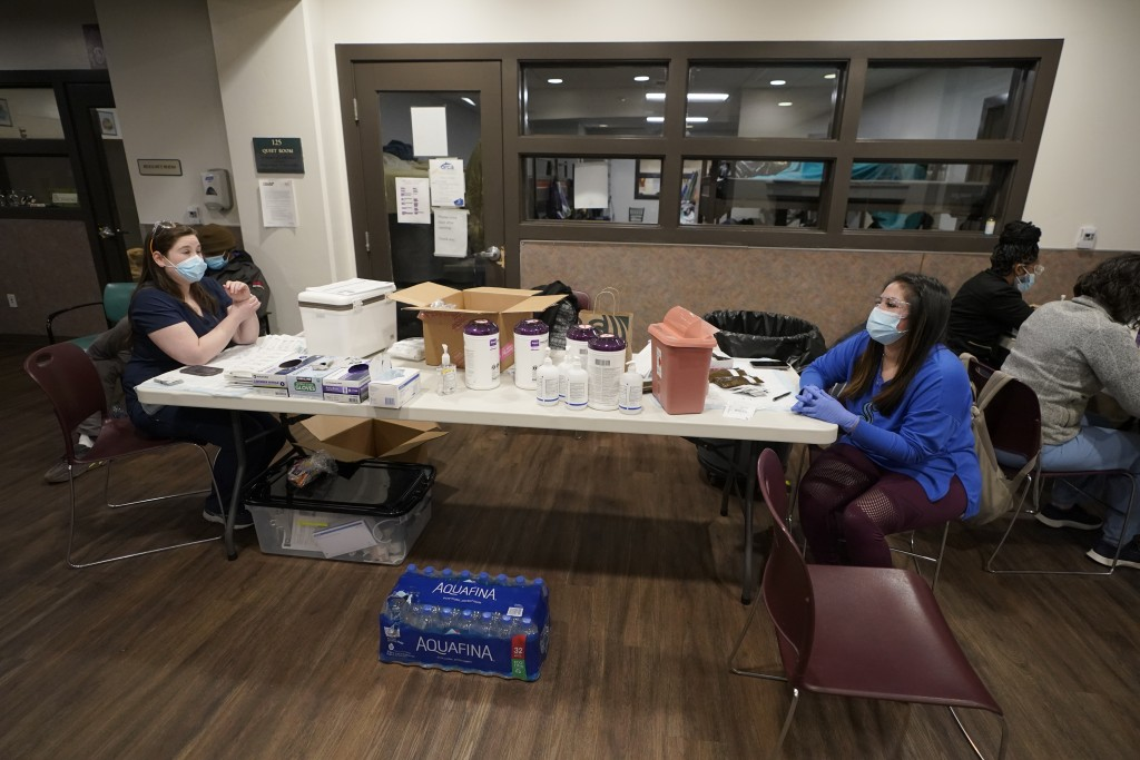 Aurora Artman, right, a medical assistant at Harborview Medical Center, talks with a colleague as they work Wednesday, April 7, 2021, at a COVID-19 va...