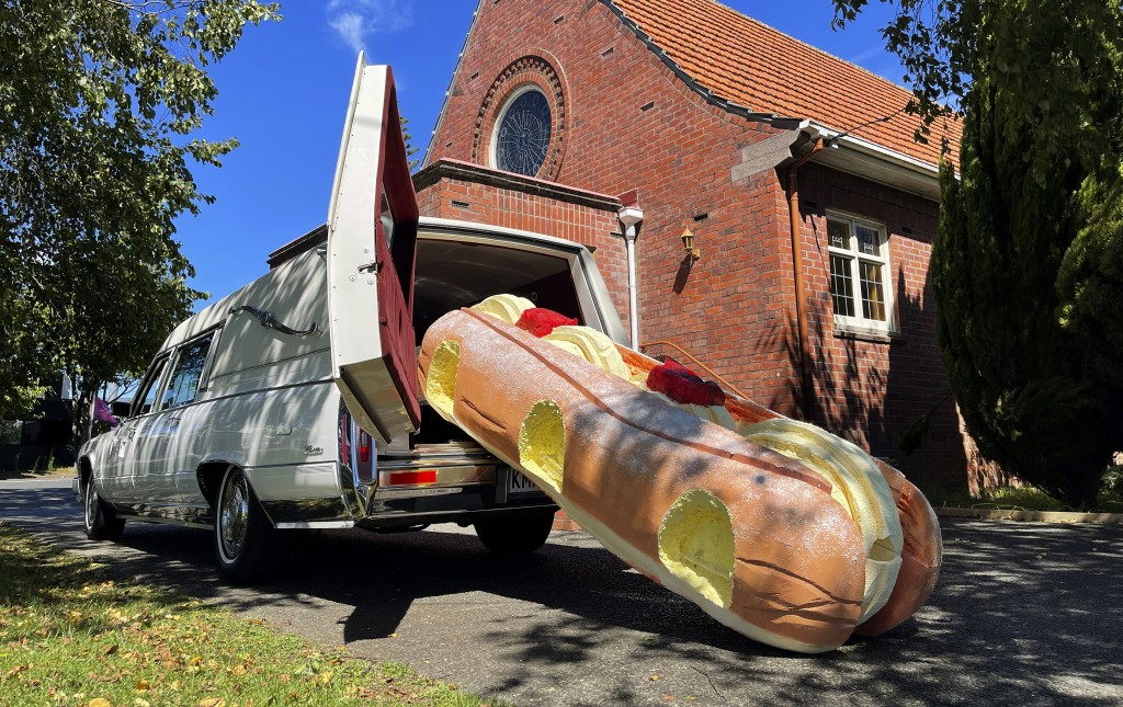 This photo provided by Ross Hall, shows a cream doughnut shaped coffin for the funeral of Phil McLean outside a church in Tauranga, New Zealand on Feb...